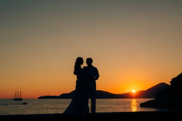 Silhouette of a newlywed couple at the sea at sunset. Wedding in Montenegro. Silhouettes of the couple, the bride and groom.