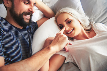 Couple lying in bed, fooling around, man poking woman's nose