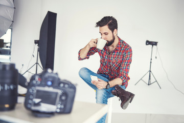 Male photographer drinking coffee and looking at smartphone in studio