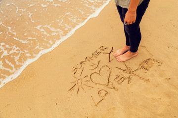 Sun and love drawing in the sand of ocean / sea beach.
