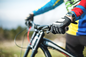 Close-up of a rider's hand in gloves on a mountain bike handlebars