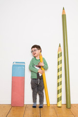 Young boy standing, holding giant size pencil, giant stationery leaning on wall beside him