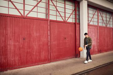 Young man in urban area, bouncing basketball, Bristol, UK