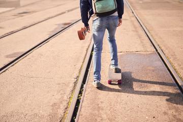 Young man skateboarding between tramlines, rear view, low section, Bristol, UK