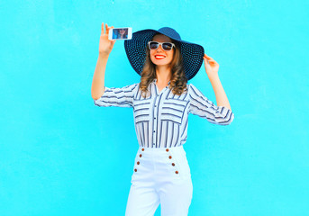 Fashion young smiling woman is taking a picture on a smartphone wearing a straw summer hat, white pants over colorful blue background