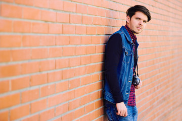 Young and handsome guy stands by a brick wall and takes pictures on a mirrorless camera