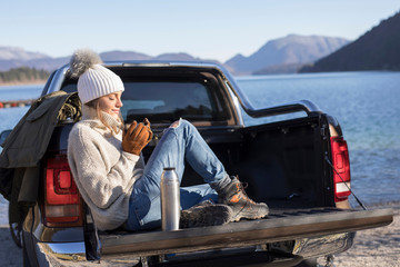 Woman with coffee sitting on pick up at lakeside in Bavarian Alps