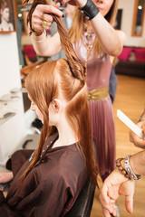 Female customer having long red hair twisted in hair salon