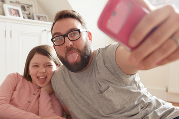 Mid adult man and daughter taking smartphone selfie