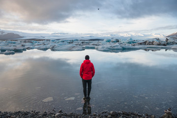 Rear view of male tourist looking out at icebergs on glacial lagoon, Jokulsarlon, Iceland