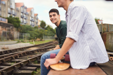 Two young men sitting by train track, Bristol, UK