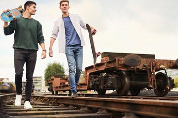 Two young men walking along train track, carrying skateboards, Bristol, UK