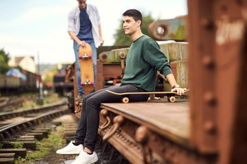 Two young men by train track, carrying skateboard, Bristol, UK
