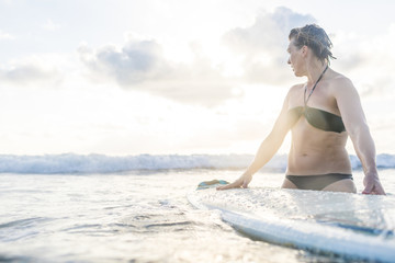 Woman with surfboard in sea looking over her shoulder, Nosara, Guanacaste Province, Costa Rica