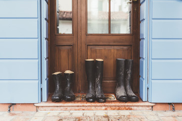 Three pairs of rubber boots on doorstep