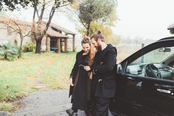 Couple leaning against car looking at smartphone