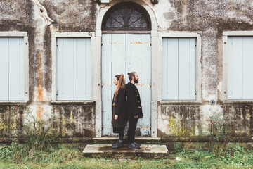 Portrait of couple standing back to back at doorway of old house