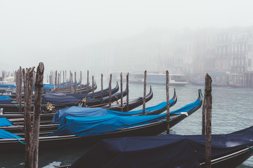 Rows of gondolas on misty canal, Venice, Italy