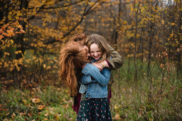 Mother and daughter hugging in wooded area, Lakefield, Ontario, Canada