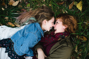 Mother and daughter lying on grass making funny faces