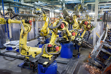 Robots welding body panels on production line in car factory