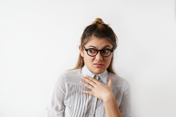 Headshot of disgusted female in striped shirt and glasses experiencing hostility to his colleagues in office and condemns her appearance. Hand on chest, raising brows. Negative people expressions
