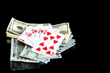 playing cards and dollars on a black background.