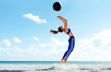 Young woman training, jumping mid air with exercise ball on beach