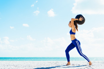 Young woman training, preparing to throw exercise ball on beach