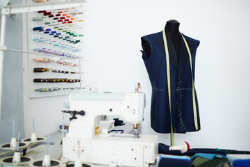 Dummy with unfinished jacket on and sewing-machine in empty dressmaker workshop