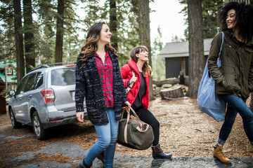 Three friends walking away from car, carrying weekend bags