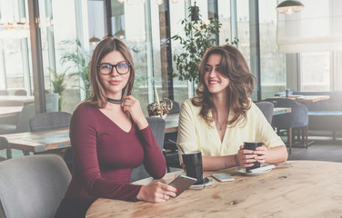 Two attractive young brunette women sit in cafe at table and drink coffee. Meeting friends at restaurant.