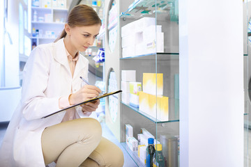 Confident pharmacist doing inventory at drug store