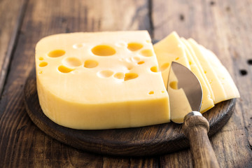 Delicious Swiss yellow cheese on dark wooden rustic background closeup