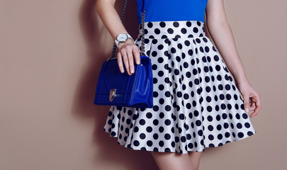 Wall Mural - Fashionable girl in polka dots dress with blue bag. Close up