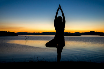 Silhouette a woman playing yoga on twilight. Sunset sky background