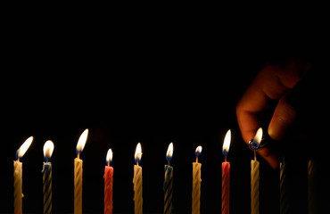 Human hand is lighting the birthday candle in the darkness