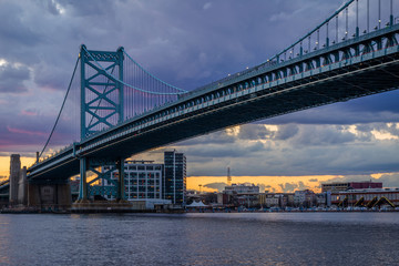 The Benjamin Franklin Bridge and and Delaware River at sunset, seen from Camden, New Jersey.