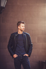 fashionable young man in a leather jacket posing in the street