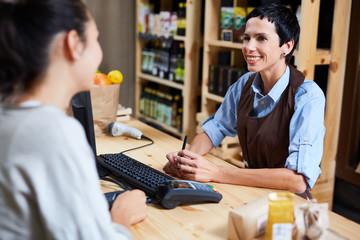 Smiling vendor talking to customer in supermarket