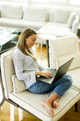 Woman using a laptop while relaxing on the couch in the room
