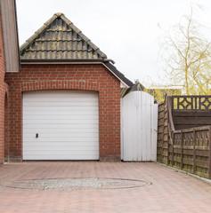Garage mit Pfannendach und weißem Tor