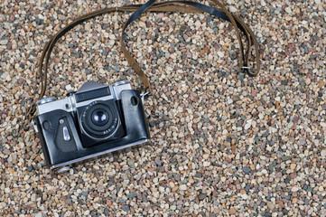 Retro camera on a stony beach