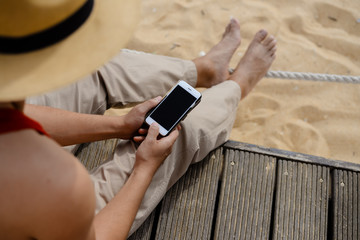 Hands holding mobile phone, sandy beach background. Person barefoot sitting feeling relax, closeup image
