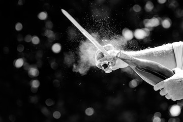 Close up image of a bottle of champagne being opened with a sword, also called sabrage