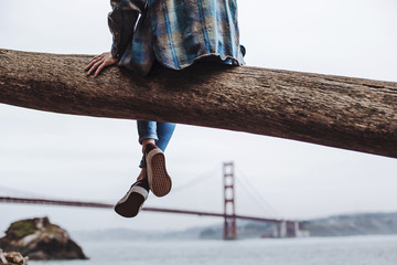 Back view of a person sitting on a tree branch with a view over San Francisco Bay and the Golden Gate bridge.