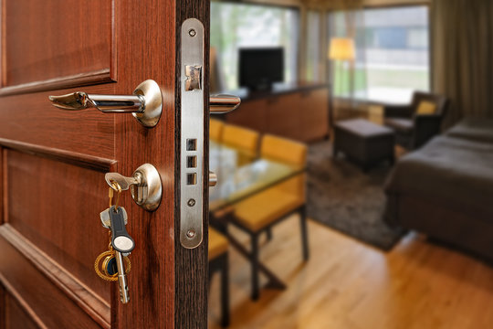 Slightly opened wooden door with group of modern keys on keychain as a concept for home ownership or for security and door policy privacy