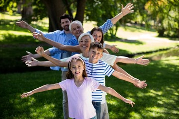 Multi generation family standing in a row with arms outstretched