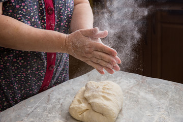 Female hands sprinkling flour over dough in the home kitchen.