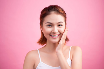 Portrait of a beautiful smiling young woman with natural make-up. Skincare, healthcare. Healthy teeth. Studio shot. Isolated on Pink Background.
